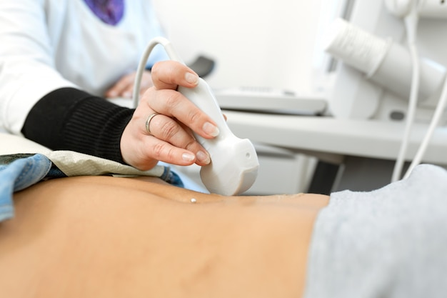 Médico em close-up realiza diagnóstico por ultrassom do abdômen e dos órgãos internos do paciente