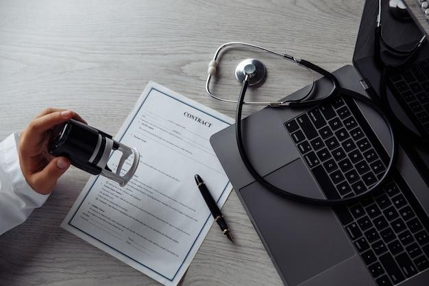 Médico em consultório médico público carimbando documento médico