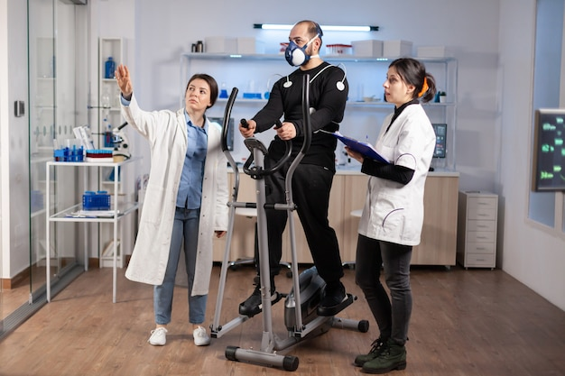 Médico em desempenho esportivo e atleta olhando para uma tela com eletrodos fixados ao corpo no treinamento cruzado, esporte vo2, ekg, freqüência cardíaca cardiovascular. ginásio de experiência de fitness.