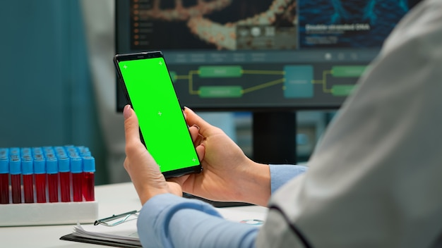 Médico em laboratório científico, segurando o telefone com tela verde, vestindo jaleco branco, enquanto a enfermeira trazendo amostras de sangue. especialista em saúde em laboratório moderno usando smartphone com maquete de exibição de chroma key
