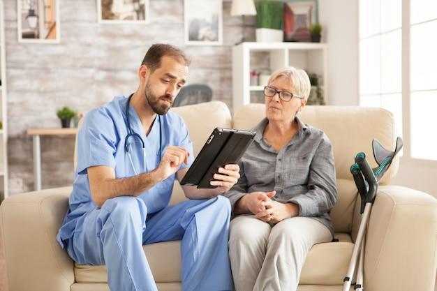 Médico em lar de idosos usando computador tablet enquanto toma com a aposentada.