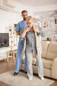 Médico em lar de idosos vestindo uniforme azul, ajudando a mulher sênior a se vestir.