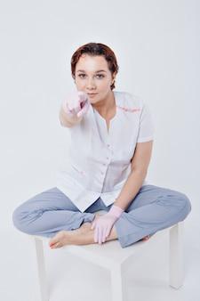 Médico em luvas de borracha mostra um ponto do dedo. uma garota usa equipamento de proteção durante uma epidemia. anúncios de anti-sépticos e equipamentos médicos em um fundo branco. treinamento sobre a importância da higiene