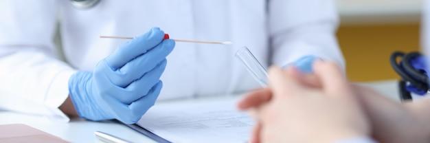 Médico em luvas de proteção segurando um tubo de ensaio na frente do paciente