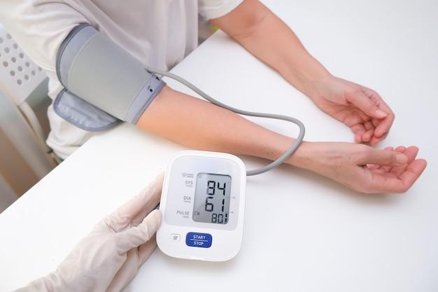 Médico em luvas mede a pressão arterial de uma pessoa, fundo branco. hipotensão arterial. mão e tonômetro fecham.