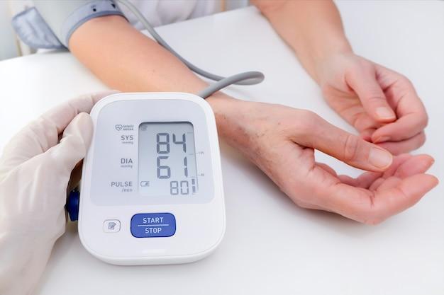 Médico em luvas mede a pressão arterial de uma pessoa