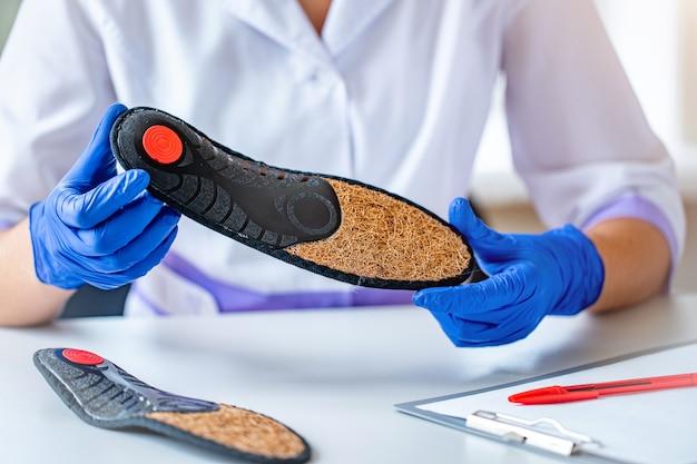 Médico em luvas médicas de borracha segura uma palmilha ortopédica para tratamento e prevenção de pés chatos durante consulta médica