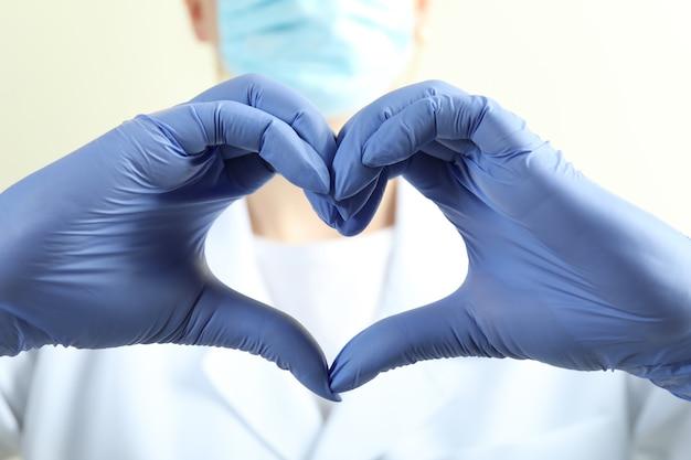 Médico em luvas médicas mostra formato de coração