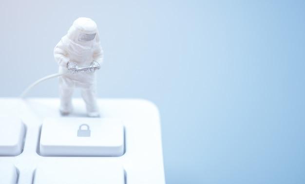 Médico em miniatura no traje de proteção individual em pé no teclado. felizmente, trancar a cidade retardará a propagação da infecção na crise do século 19.