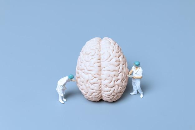 Médico em miniatura verificando e analisando a doença de alzheimer e a demência do cérebro, conceito de ciência e medicina
