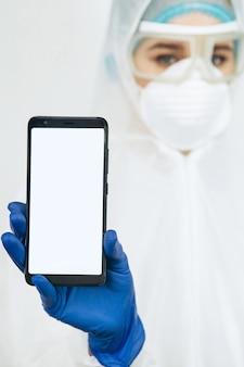 Médico em roupas de proteção, um respirador, óculos, luvas segura um telefone. os médicos pediram para ficar em casa durante a epidemia de coronavírus. covid-19