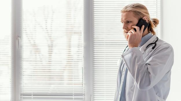 Médico em tiro médio falando ao telefone