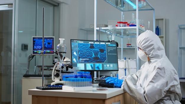 Médico em traje de ppe, olhando para uma amostra de sangue em tubo de ensaio, sentado em um laboratório equipado. cientista que trabalha com várias bactérias e tecidos, conceito de pesquisa farmacêutica para antibióticos contra covid 19