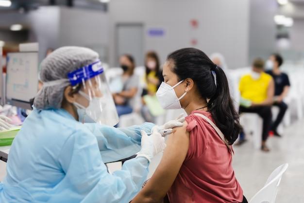 Médico em traje de proteção dando ao paciente uma vacina para a doença do coronavírus