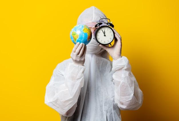 Médico em traje de proteção e máscara segura o globo da terra e despertador