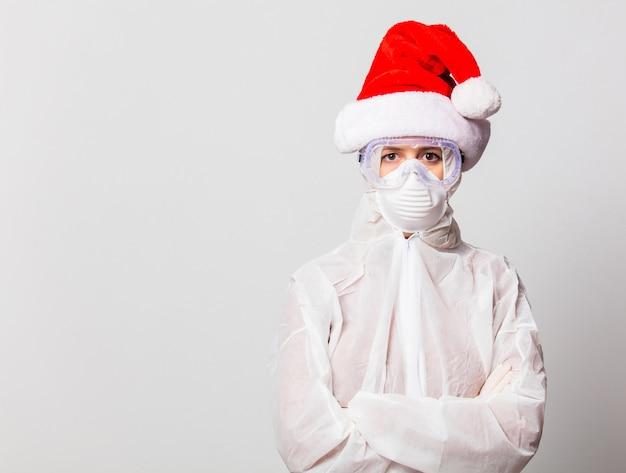 Médico em traje de proteção e óculos com máscara e chapéu de natal