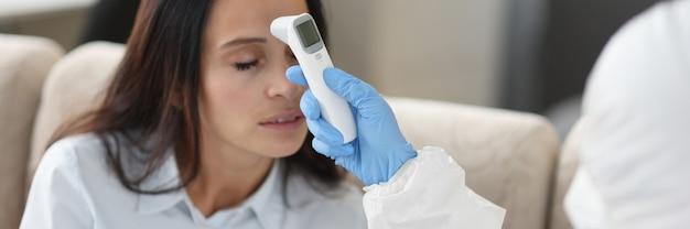Médico em traje de proteção mede a temperatura com termômetro infravermelho sem contato