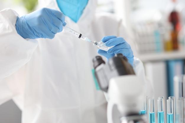Médico em traje de proteção puxa líquido para a seringa. vacinação da população contra o conceito de coronavírus