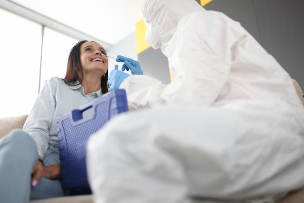 Médico em traje de proteção tomando cotonete para coronavírus do paciente