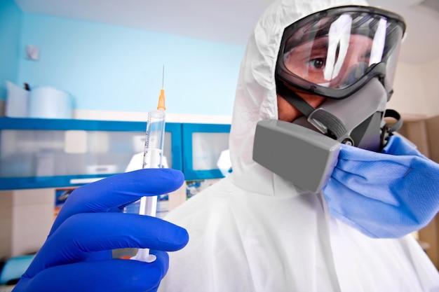 Médico em traje de proteção uniforme e máscara detém a seringa de injeção com vacina.