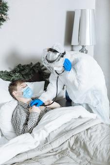 Médico em um traje de proteção de epp, máscara e luvas ouve a respiração do paciente com um estetoscópio em casa antes do ano novo e do natal