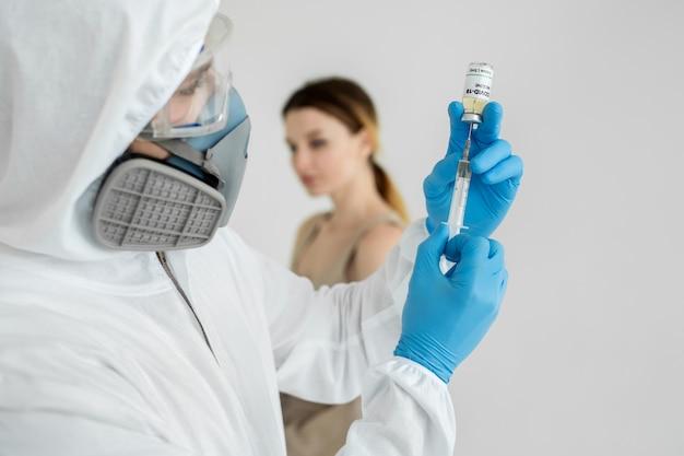 Médico em um traje de proteção e máscara detém uma seringa de injeção e vacina covid-19. homem em traje de proteção injeta uma mulher do coronavírus.