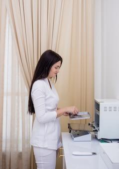 Médico em um uniforme branco coloca os instrumentos em um dispositivo de esterilização no consultório