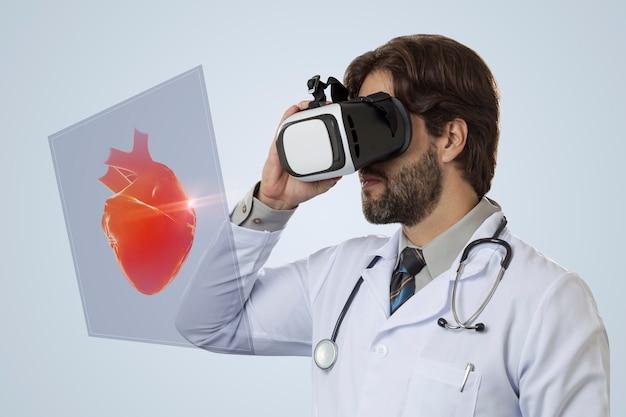 Médico em uma parede cinza usando óculos de realidade virtual, olhando para um coração virtual