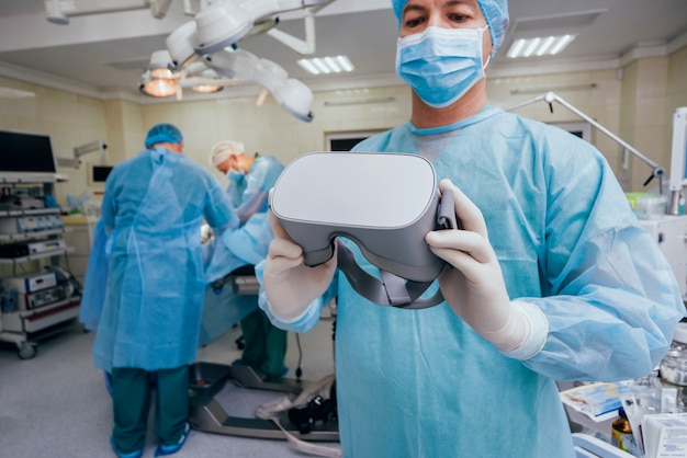 Médico em uma sala cirúrgica com óculos de realidade virtual no fundo da operação real.
