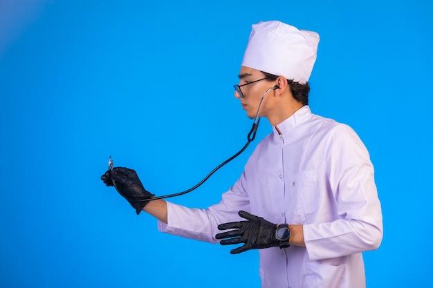 Médico em uniforme médico branco verificando com estetoscópio máscaras na mão sobre fundo azul
