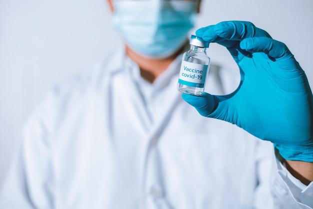 Médico, enfermeira e cientista com luvas azuis segurando a vacina contra a gripe