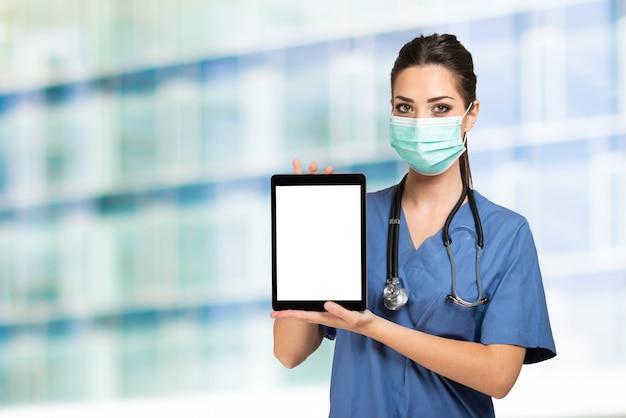 Médico enfermeira mascarada mostrando um tablet com uma tela branca