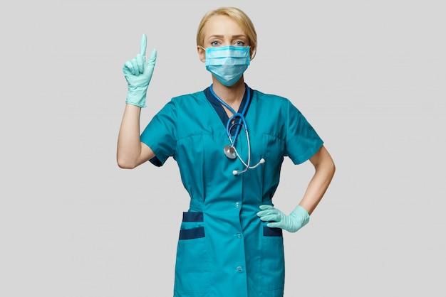 Médico enfermeira mulher vestindo máscara protetora e luvas de látex - aponte um dedo para copyspace vazio