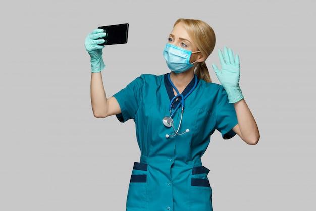 Médico enfermeira mulher vestindo máscara protetora e luvas de látex - fazendo videochamada no telefone