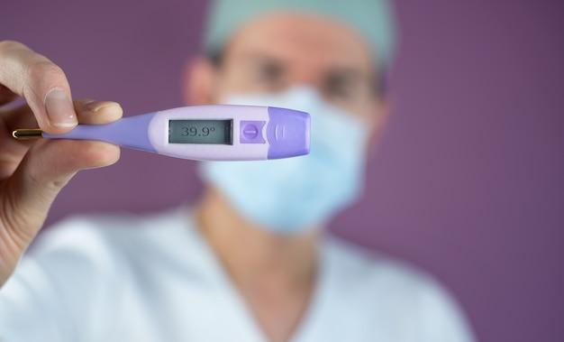 Médico enfermeira olhando um paciente com temperatura com um termômetro por causa do coronavirus covid-19