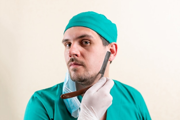 Médico engraçado com uma navalha nas mãos