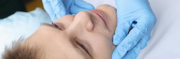 Médico enluvado examina o rosto de jovens problemas de pele facial no conceito de homens
