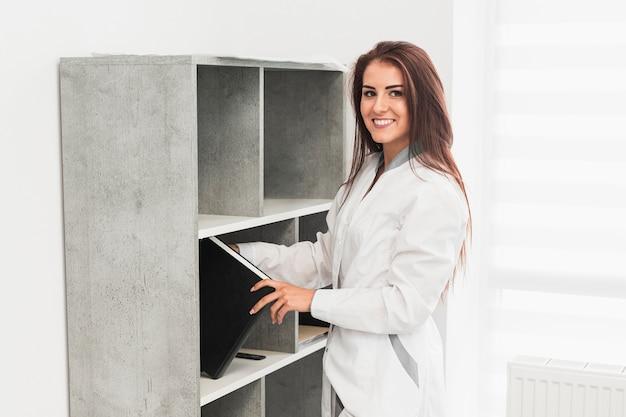 Médico, escolhendo um arquivo da prateleira