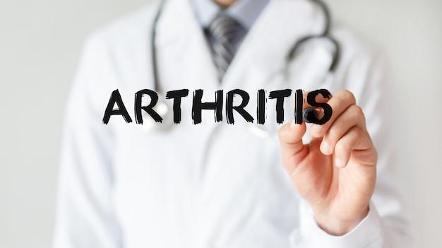 Médico escrevendo a palavra artrite com marcador, conceito médico