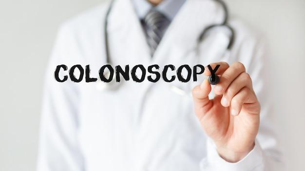 Médico escrevendo a palavra colonoscopia com marcador, conceito médico