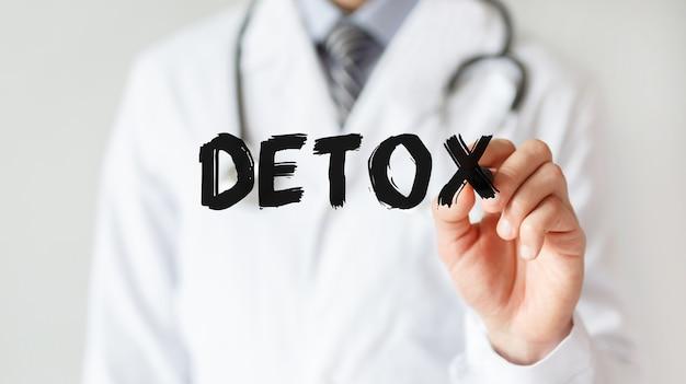 Médico escrevendo a palavra detox com marcador, conceito médico