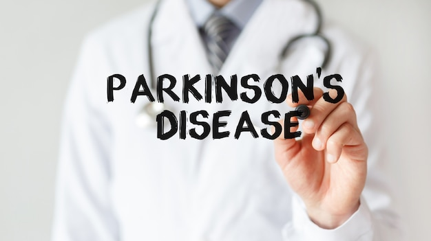Médico escrevendo a palavra doença de parkinson com marcador