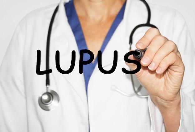 Médico escrevendo a palavra lupus com marcador, conceito médico