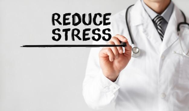Médico escrevendo a palavra reduzir o estresse com marcador, conceito médico