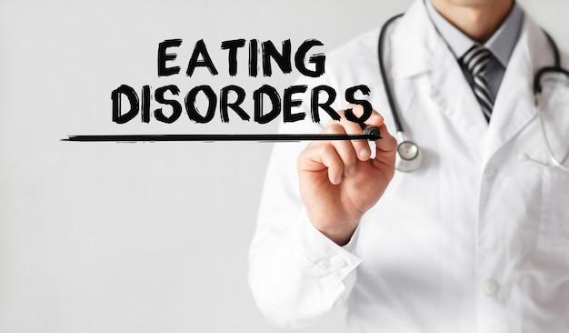 Médico escrevendo a palavra transtornos alimentares com marcador, conceito médico