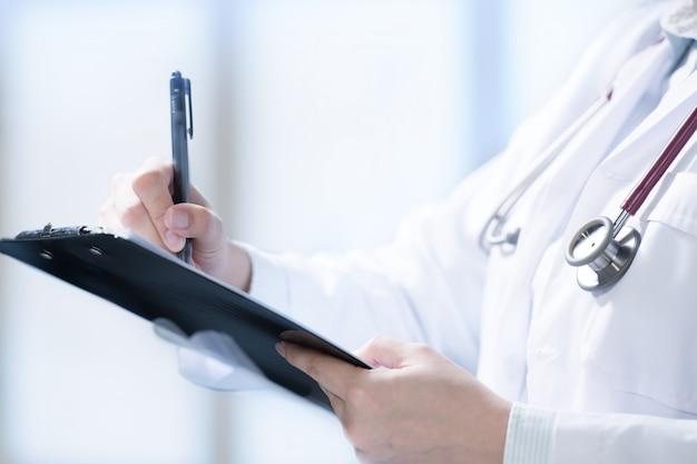 Médico, escrevendo e tomando notas no cliboard em ambiente hospitalar