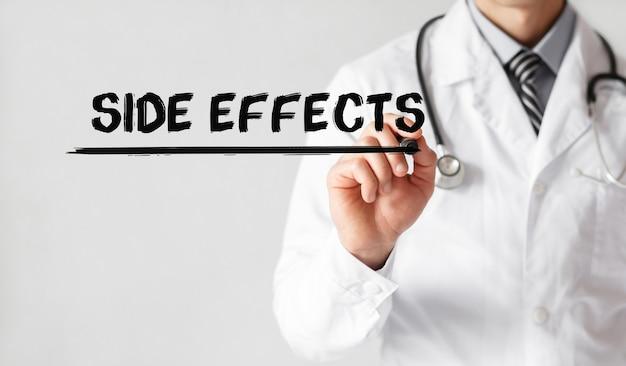 Médico escrevendo efeitos colaterais de palavras com marcador, conceito médico