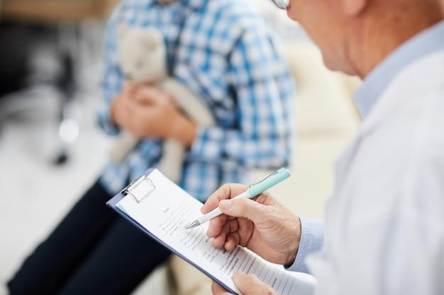 Médico escrevendo na área de transferência