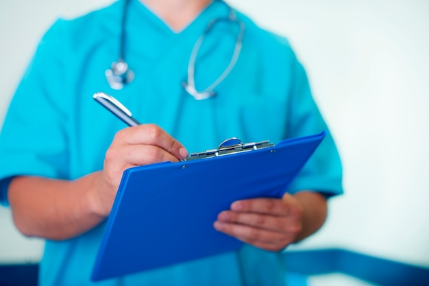 Médico escrevendo no prontuário