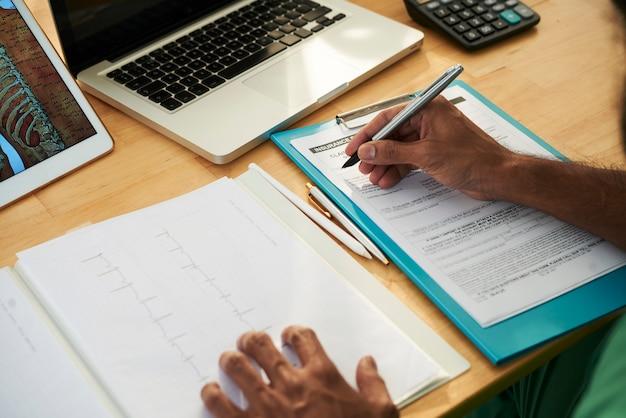 Médico escrevendo notas médicas